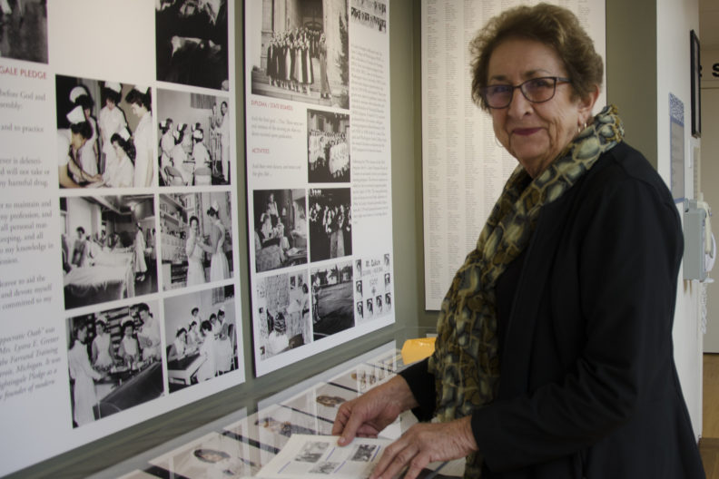 Janet Holloway stands in front of a display of nursing memorabilia at St. Luke's Rehabilitation Institute