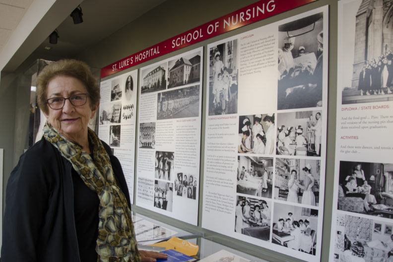 Janet Holloway stands in front of a new display of nursing history.