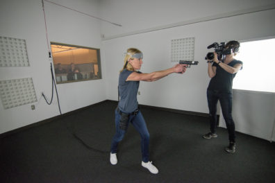 Robin Hauser points a laser handgun while participating in Counter Bias Training Simulation on the campus of WSU Spokane.