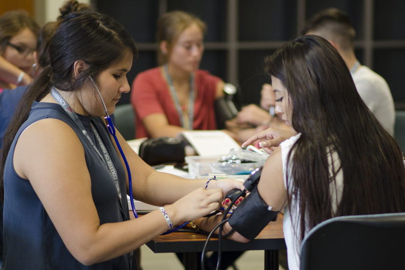 A counselor shows a teenage participant in Na-ha-shnee Native American Health Sciences Institute how to measure blood pressure.