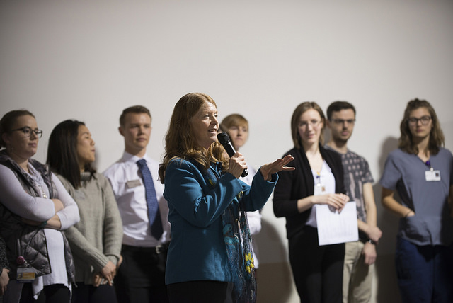 Portrait of Barb Richardson holding a microphone with a group of teenagers behind her.