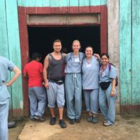 Four students stand in front of a rural clinic in Peru.