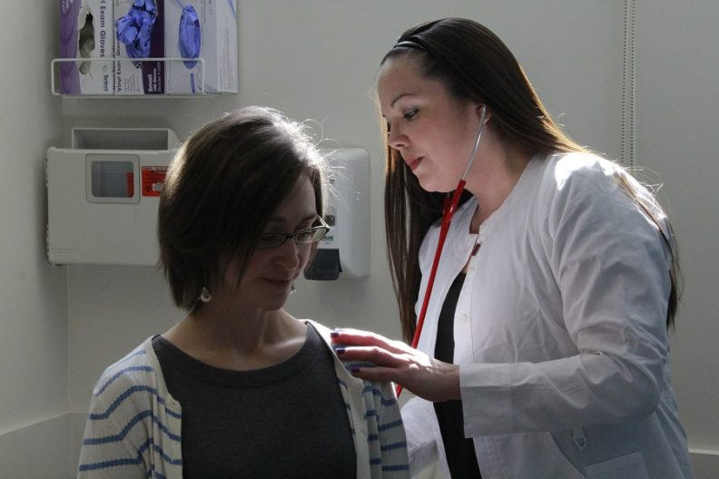 Portrait of a nurse practitioner using a stethoscope on a patient.