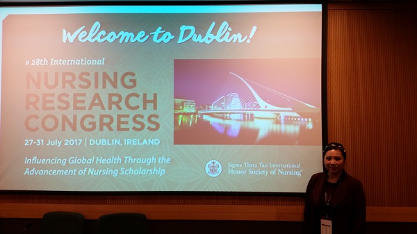 Dr. Connie Nguyen-Truong standing in front of a Welcome to Dublin sign at the International Nursing Research Conference