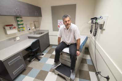 Mike Munoz sits on an exam table in the WSU College of Nursing's Simulation Lab.