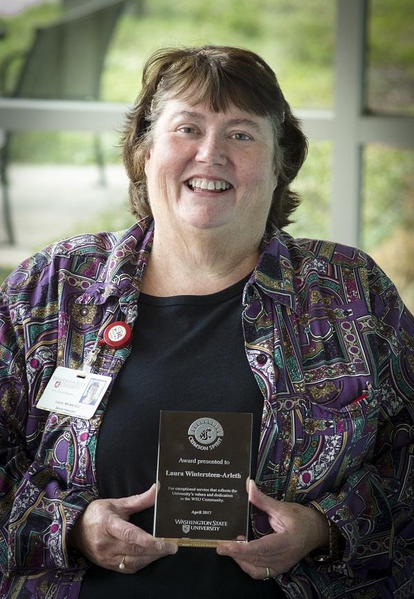 Portrait of Laura Wintersteen-Arleth holding the Crimson Spirit Award.