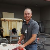 Mike Mosier with a knife and piece of deer meat.