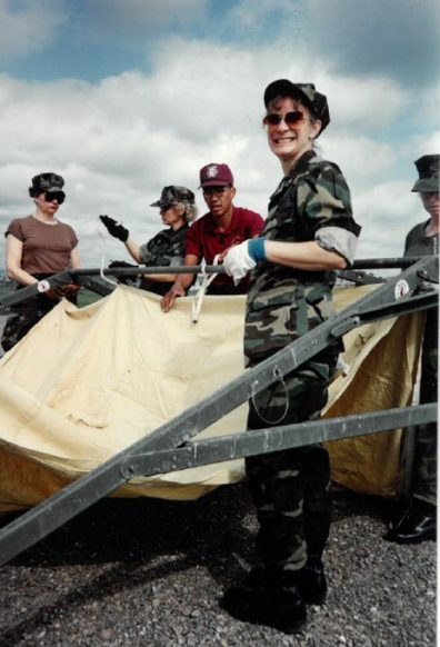 Picture of Denise Smart in camo helping put up a tent.