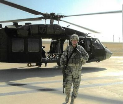 Chris Nelson in full camo standing next to a helicopter