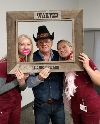Bill Bunch and two nursing students with Old West props at pig roast.