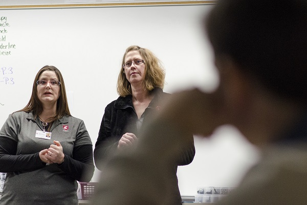 Two nursing students standing in front of a classroom.