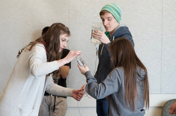 Students holding IV bags.