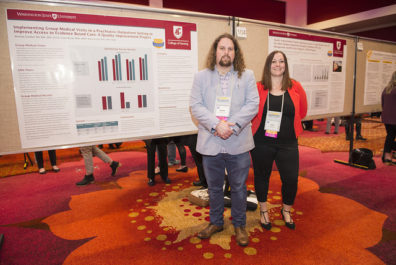 Two people standing next to research posters.
