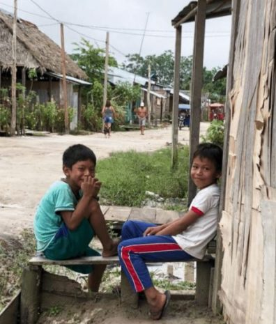 two kids sitting on a road in Peru