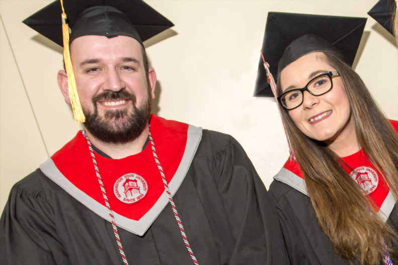 portrait of two students in cap and gown