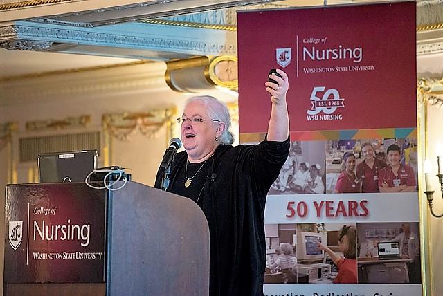 Portrait of speaker gesturing at podium