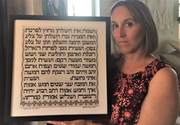 Heather Kriss holding image of her Torah panel