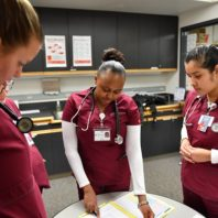 Three nursing students looking at a document.
