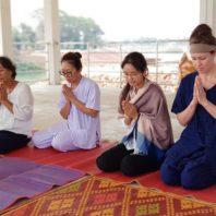 four people praying in Thailand