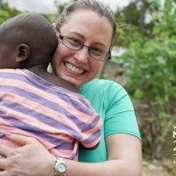 Pam Martin holds child while on a medical volunteer mission to Haiti in 2017
