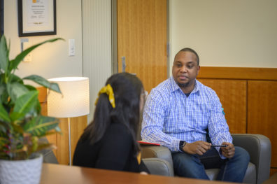 Nurse practitioner student talks to a person in an office