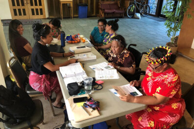 Group of Marshallese people sitting around a table.