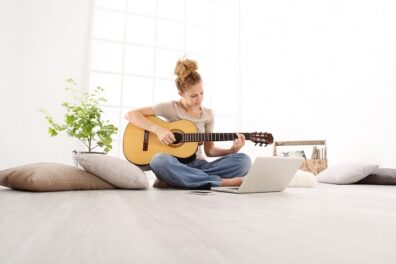 woman learning to play guitar online