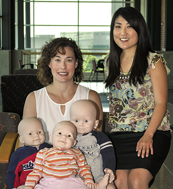 terriff and song pose with dummy babies