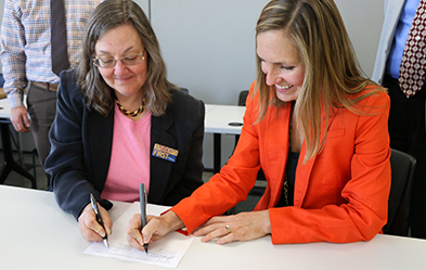 Heritage University Provost Laurie Fathe, left, and WSU College of Pharmacy Assistant Dean for Recruitment and Student Success Jennifer Robinson sign agreements. (Photo by David Mance, Heritage University)