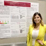Yadira Pérez-Páramo stands by her research poster