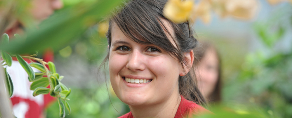 closeup of smiling student with green leaves all around