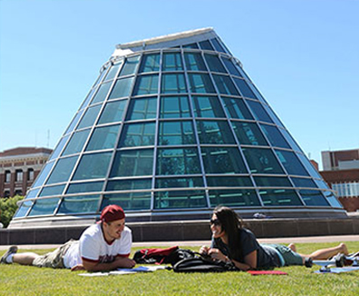 Two students study lying in grass near Terrell Library dome