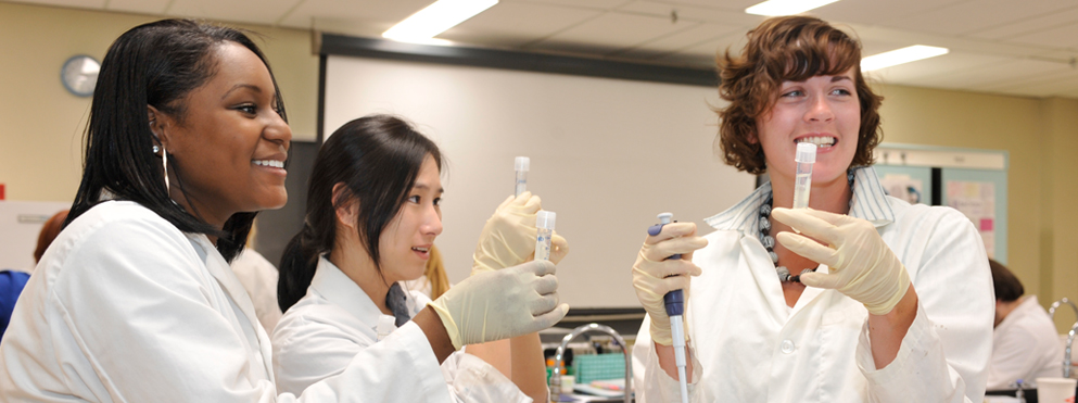 three students in lab coats hold capped test tubes