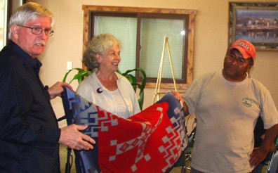 With Orlan Svingen to her right, Janet Creighton was presented with a specially embroidered Pendleton blanket by Leo Ariwite, a prominent member of the Agai Dika, mixed-band of Shoshone, Bannock and Sheepeater tribes, in an appreciation event at the Sacajawea Interpretive, Cultural, and Educational Center in Salmon, Idaho, in 2013. Photo credit: Mary Ghirardo