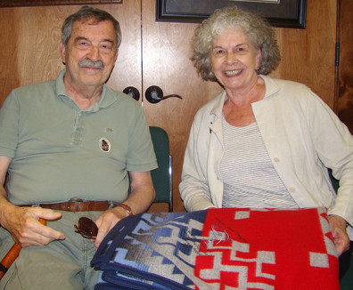The Creightons smile over their blanket, which is embroidered with the image of a salmon and the words: John and Janet Creighton: Laureates of WSU and friends of the Agai Dika, Sacajawea's People, 2013. Photo credit: Mary Ghirardo