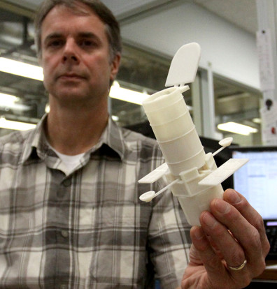 Dave Savage holds a miniature, 3D-printed Hubble Telescope in the Technical Services Instrument Shop.