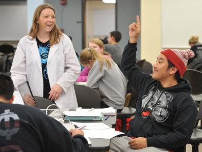 Math Learning Center student raises hand, smiling tutor in background