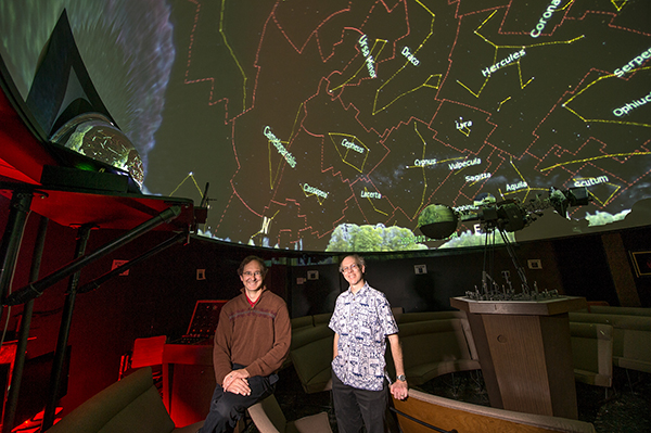 Michael Allen, planetarium director and senior instructor of physics and astronomy, and Guy Worthey, associate professor of physics and astronomy, stand beneath the dome of WSU's planetarium.