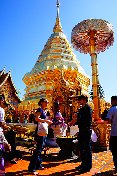 """Van Elsberg and Cassaniti make """"merit"""" at Wat Phrathat Doi Suthep monastery in the hills overlooking Chiang Mai in Thailand. Merit is a concept in Buddhism that suggests a person can transfer accumulated goodwill to a deceased loved one in order to diminish the deceased's suffering in their new existence."""