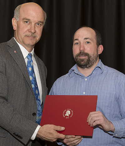 Bryan Fry, right, accepts the CAS Award for Excellence in Teaching from Dean Daryll DeWald.