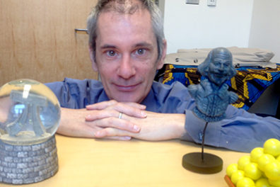 Thomas Gazzola, who is framed between the mathematical symbol Pi and a William Shakespeare statuette