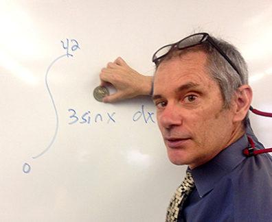 Tom Gazzola doing mathematics at chalkboard