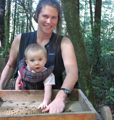 Shannon Tushingham gets a little hand from her baby at an archaeological excavation site.