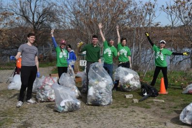 Bateman Island cleanup crew celebrate the large bags of trash they removed from the site..