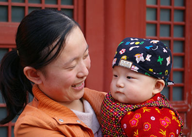 Asian mother smiling and holding an infant child.