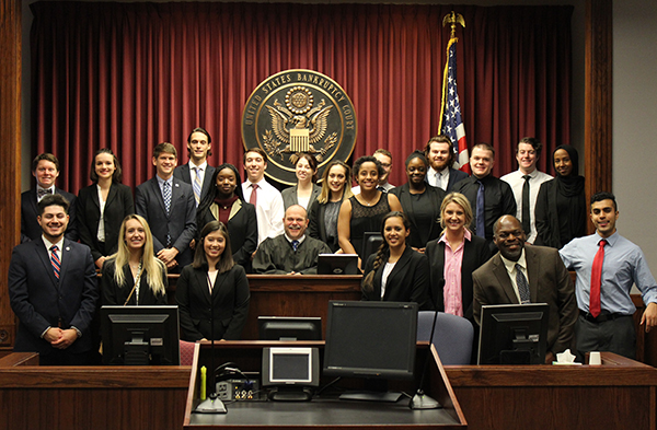 Mock Trial students and faculty co-advisor Aman McLeod pose with Tim Siler at the judge's bench flanked by the U.S. flag and court's seal.
