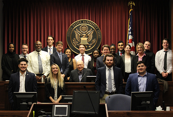 Mock Trial students and faculty co-advisor Aman McLeod pose with Judge John Rossmeissl at the judge's bench flanked by the U.S. flag and court's seal.