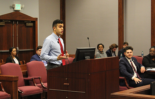 A mock trial team member enthusiastically presents his case as other students look on.