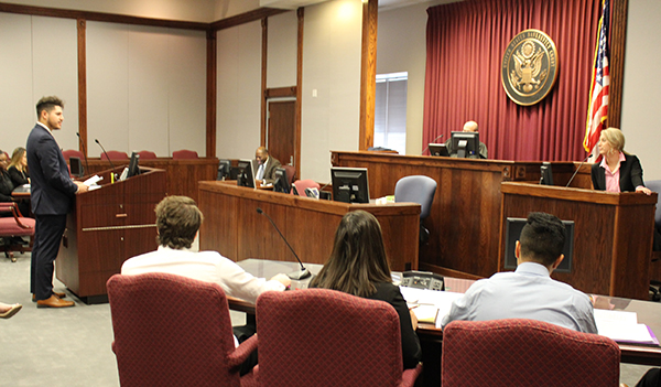 "A mock trial team member questions a ""witness"" before the ""judge"" and other student ""attorneys."""