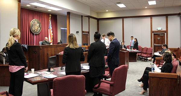 "Mock Trial team members, dressed for success, stand before the ""judge"" as he speaks."
